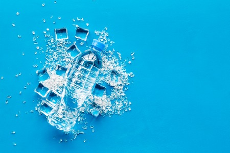Frozen water in ice cubes and plastic bottle on blue bar table top view mockup Archivio Fotografico