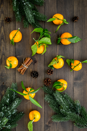 New Year and Christmas Eve with mandarins, fir tree and cinnamon . Citrus winter fruits on wooden background top view Stock Photo