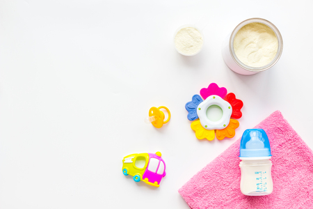 Baby care with craft toys for newborn. Rattle and powdered milk. White background top view copy space