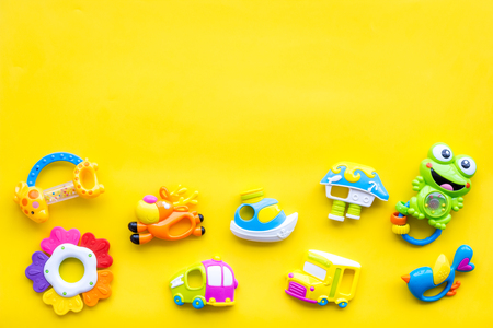 Baby care with craft toys for newborn. Rattle. Yellow background top view copy space Foto de archivo - 113743041