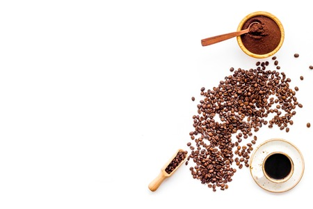 Brown roasted coffee beans scattered on white background and cup of americano top view mockup
