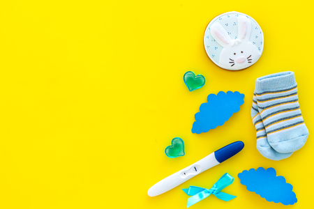 Joy of long-awaited pregnancy. Pregnancy test with socks and hearts on yellow background top view mock-up