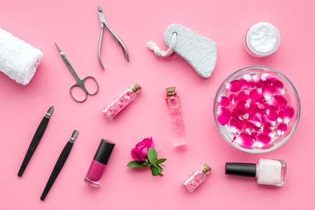 tools for manicure with spa salt and rose on pink background top view