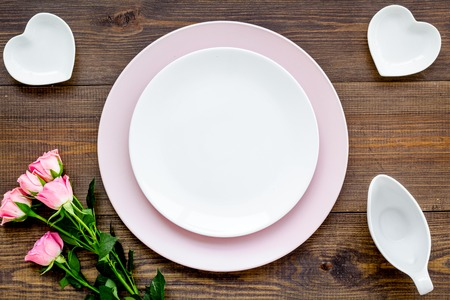 Empty pink colorful plate with flower for table setting on wooden table backgroung top view copy space