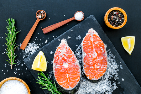Fresh salmon steak with spices, rosemary, lemon for cooking healthy food on dark background top view