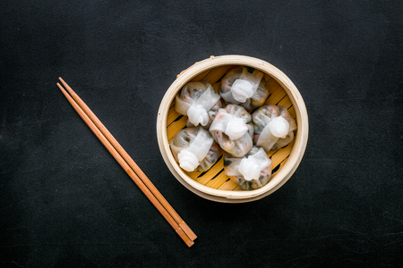 Chinese food set with dim sum, sticks on black background top view Stock Photo