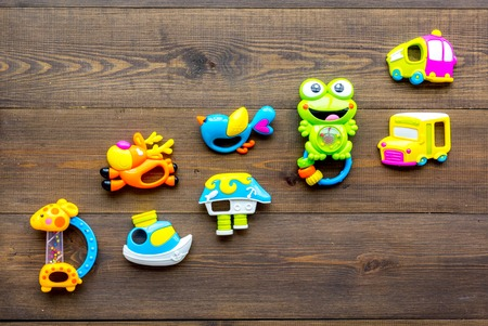 Baby care with craft toys for newborn. Rattle. Wooden background top view copy space Foto de archivo - 113857534
