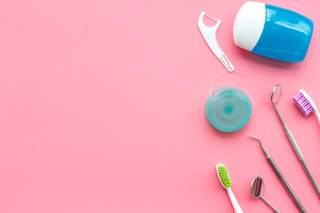 Daily oral hygiene for family. Toothbrush, dental floss and dentist instruments on pink background top view mock up