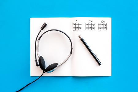 Desk of musician for songwriter work with headphones and notes blue background top view