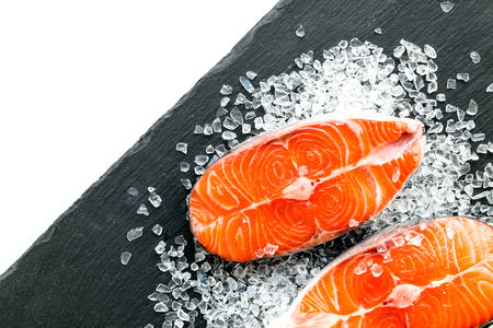 Raw salmon steak on black plate for cooking on white background top view