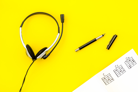Desk of musician for songwriter work with headphones and notes yellow background top view