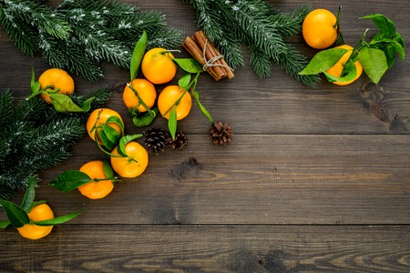 New Year and Christmas Eve with mandarins, fir tree and cinnamon . Citrus winter fruits on wooden background top view space for text Stock Photo