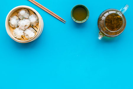 Dinner in Chinese restaurant with dim sum, sticks and herbal tea on blue background top view space for text