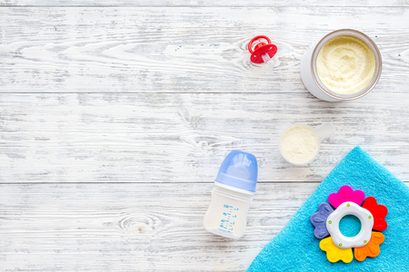 Toys for newborn baby set with plastic rattle and milk in bottle on white wooden background flat lay space for text Фото со стока