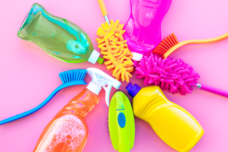 Housekeeping tool. Detergents, soap, cleaners and brush for housecleaner work on pink background top view space for text Stockfoto