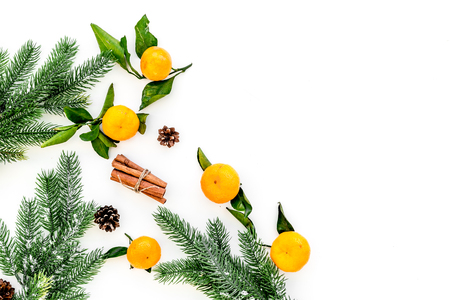pile of tangerines, fir tree and cinnamon for New Year and Christmas celebration on white background top view mock up