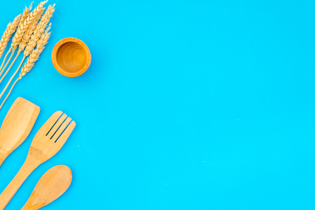 Woodenware set with bowl, spoons and forks on blue background top view mock up