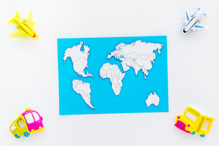 Children tourism outfit with map and toys white background flat lay