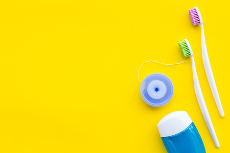 Daily oral hygiene for family. Toothbrush and dental floss on yellow background top view mock up