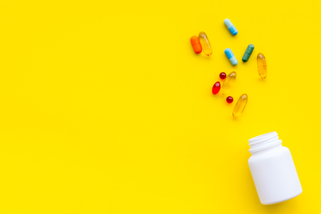 Close up of an open bottle of medicine and its lid. Several pills are lying on yellow desk. Pharmacology and medical supplies. Top view mock-up