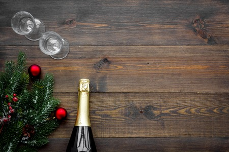 New Year celebration with spruce branch, champagne and glasses wooden table background top view mock up