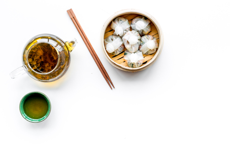 Dinner in Chinese restaurant with dim sum, sticks and tea on white background top view space for text