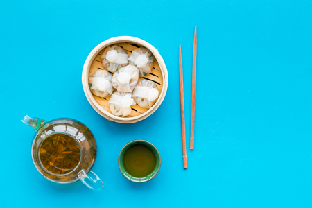 Dinner in Chinese restaurant with dim sum, sticks and herbal tea on blue background top view