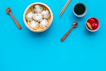Dim sums with red pepper and vegetables with sticks and black tea in Chinese restaurant on blue background top view mockup