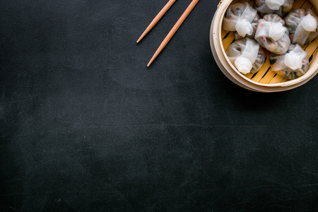 Dim sums with red pepper and vegetables with sticks in Chinese restaurant on black background top view mockup