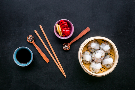 Dinner in Chinese restaurant with dim sum, sticks and tea on black background top view Stock Photo