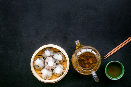 Chinese steamed dumplings Dim Sum in bamboo steamer with tea on black background top view mock up Stock Photo