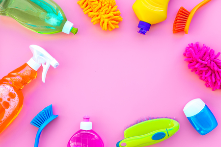 Housekeeping tool. Detergents, soap, cleaners and brush for house cleaner work on pink background top view space for text
