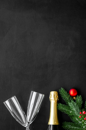 New year and Christmas party with spruce, champagne bottle and glasses on black background top view space for text