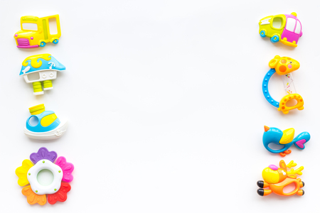 Toys for newborn baby set with plastic rattle on white background flat lay space for text Foto de archivo - 113826792