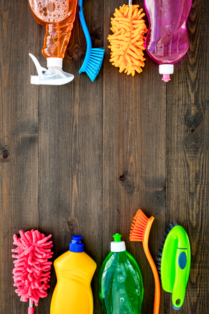 House cleaner tools set with detergents, soap, cleaners and brush on wooden background top view mock up