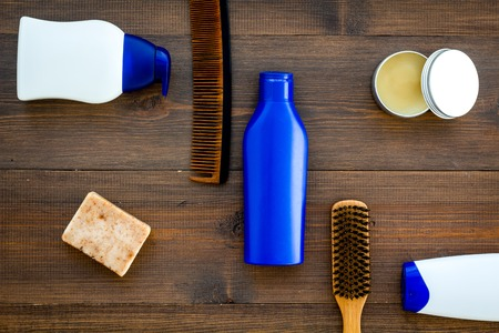 Instruments of male hairdresser with shampoo and comb in barbershop top view on wooden background mock up