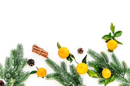 New Year and Christmas Eve with mandarins, fir tree and cinnamon. Citrus winter fruits on white background top view space for text