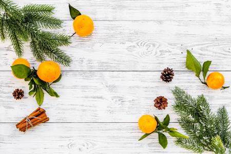New Year and Christmas Eve with mandarins, fir tree and cinnamon. Citrus winter fruits on white wooden background top view space for text
