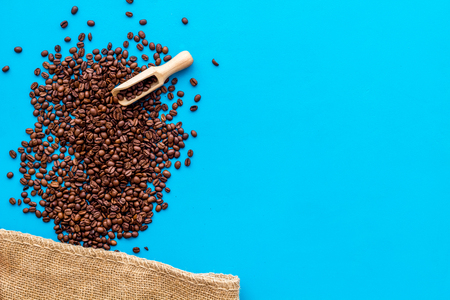 Coffee concept. Roasted beans on blue background top view copy space. Stock Photo