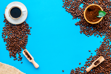 Coffee background with beans and cup of Americano on blue table flat lay space for text