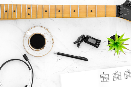 Desk of musician for songwriter work with headphones, keyboard, guitar and notes marble background top view