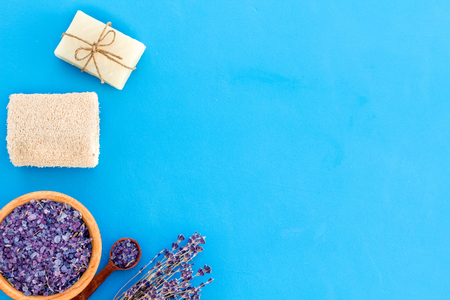 Spa set with lavender spa salt. Purple spa salt near dry lavender branches and washcloth on blue background top view space for text Stock Photo