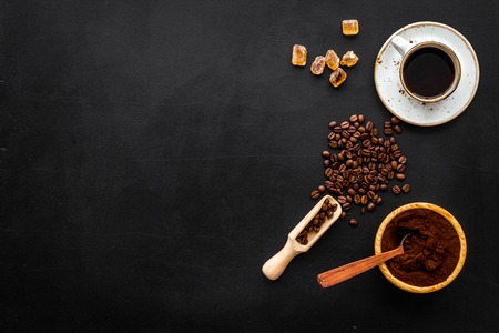 Coffee concept. Roasted beans, ground coffee on black background top view copy space Stock Photo