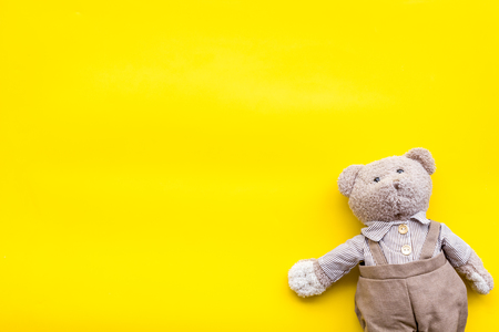 Baby care with craft toys for newborn. Teddy bear. Yellow background top view copy space