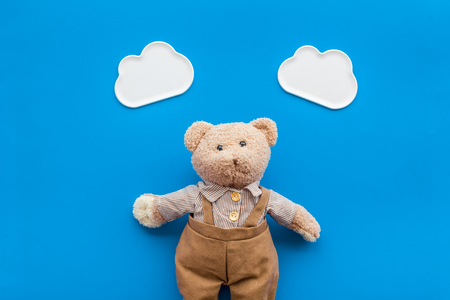 Baby care with craft toys for newborn. Teddy bear. Blue background top view
