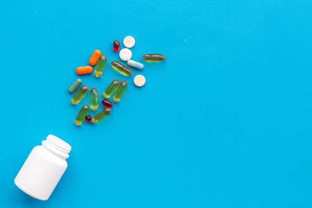 Close up of an open bottle of medicine and its lid. Several pills are lying on blue desk. Pharmacology and medical supplies. Top view mock-up Stock Photo