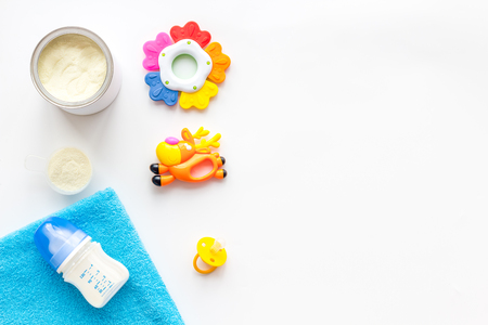 Craft toys for kids. Developing rattle for the smallest and baby bottle with milk. White background top view mock up
