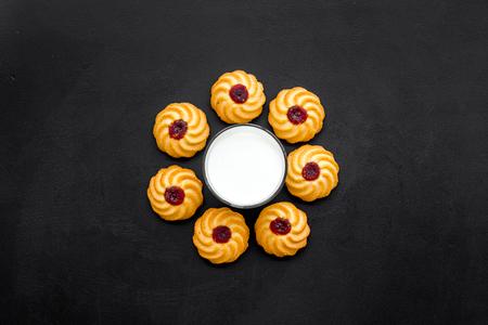 Children tradition evening dessert. Milk and homemade cookies on black background top view Reklamní fotografie