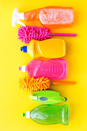 Housekeeping tool. Detergents, soap, cleaners and brush for house cleaner work on yellow background top view space for text Stockfoto