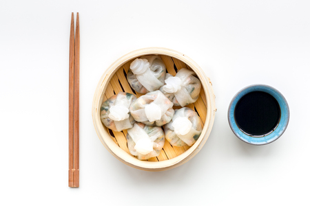 Chinese food set with dim sum, sticks and tea on white background top view
